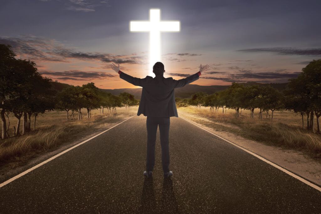 Man standing in road facing cross with hands raised