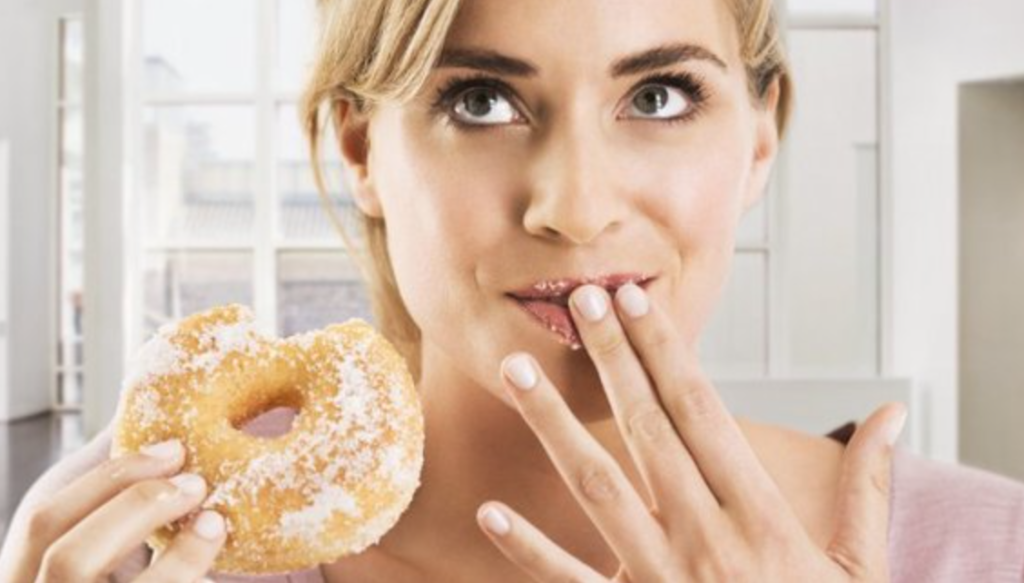 Healthy shame with woman eating donut